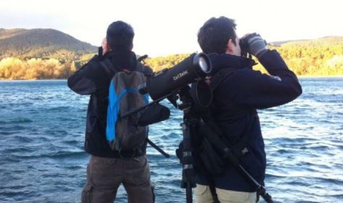 Dues persones fent observació en un llac
