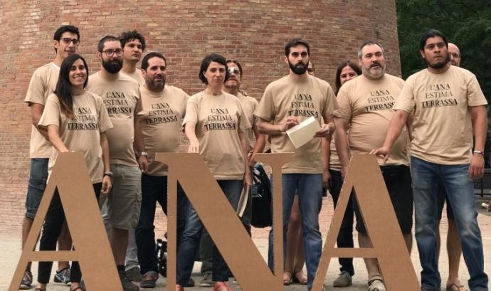 Membres d'ANA darrere del rètol amb les lletres de l'entitat