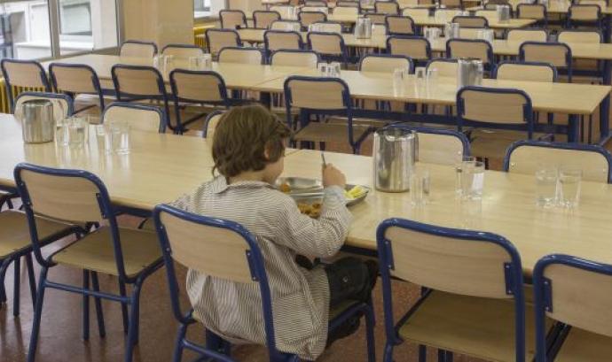 Nen menjant en un menjador escolar. Font: web elpais.com Font: