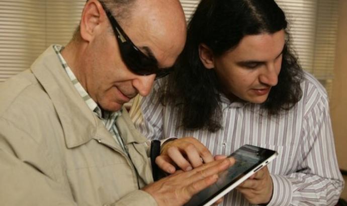 Una persona voluntària acompanyant a una persona amb discapacitat visual, usuària de l'ONCE Font: ONCE
