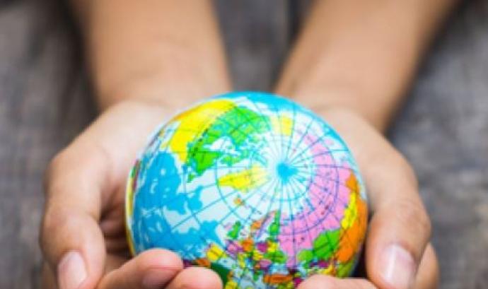 Mans voluntàries agafant un mapa del món