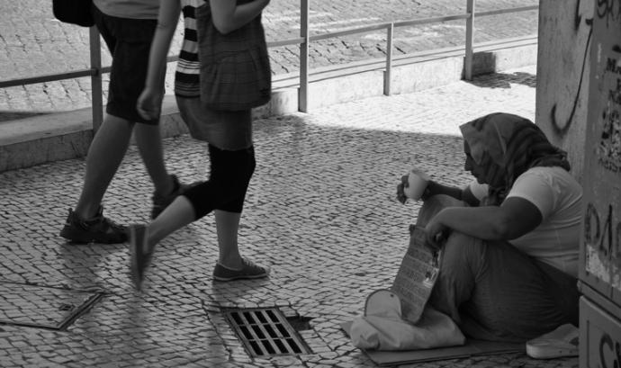 Una dona demanant en un carrer de Lisboa. Font: Wikimedia Font: