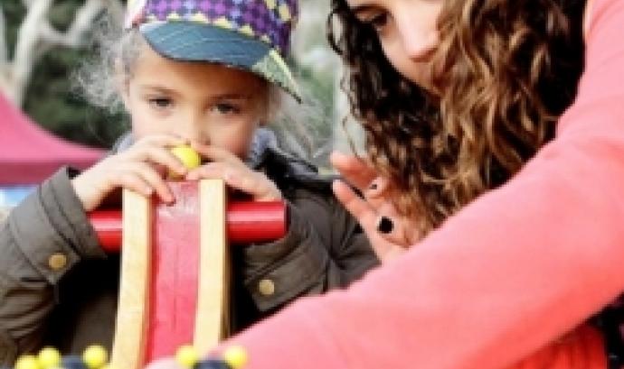 Voluntària del 'Posa't la Gorra' juga amb una nena. Font: AFANOC
