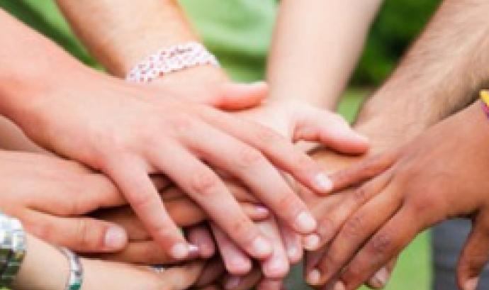 Persones voluntàries fan pinya amb les mans després d'una activitat. Font: Xarxanet
