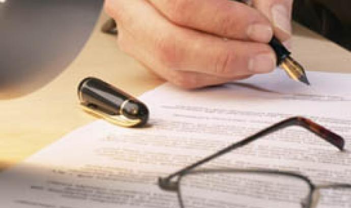 Persona signant un document Font: