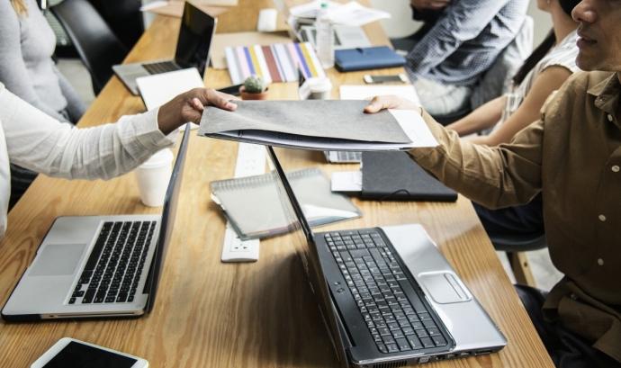 Equip treballant amb ordinadors i papers