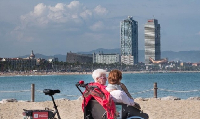Tricicle amb dues persones grans davant del mar