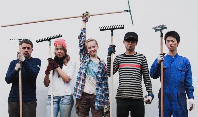 Quatre joves voluntaris sotenen eines agrícoles