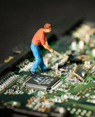 Fotografia d'una persona trencant una placa electrònica