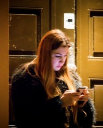 Fotografia d'una dona utilitzant un telèfon mòbil.