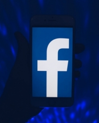 Fotografia d'una persona utilitzant un telèfon mòbil amb l'aplicació Facebook.