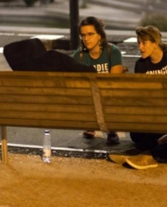 Persones oferint suport a una altra que dorm al carrer