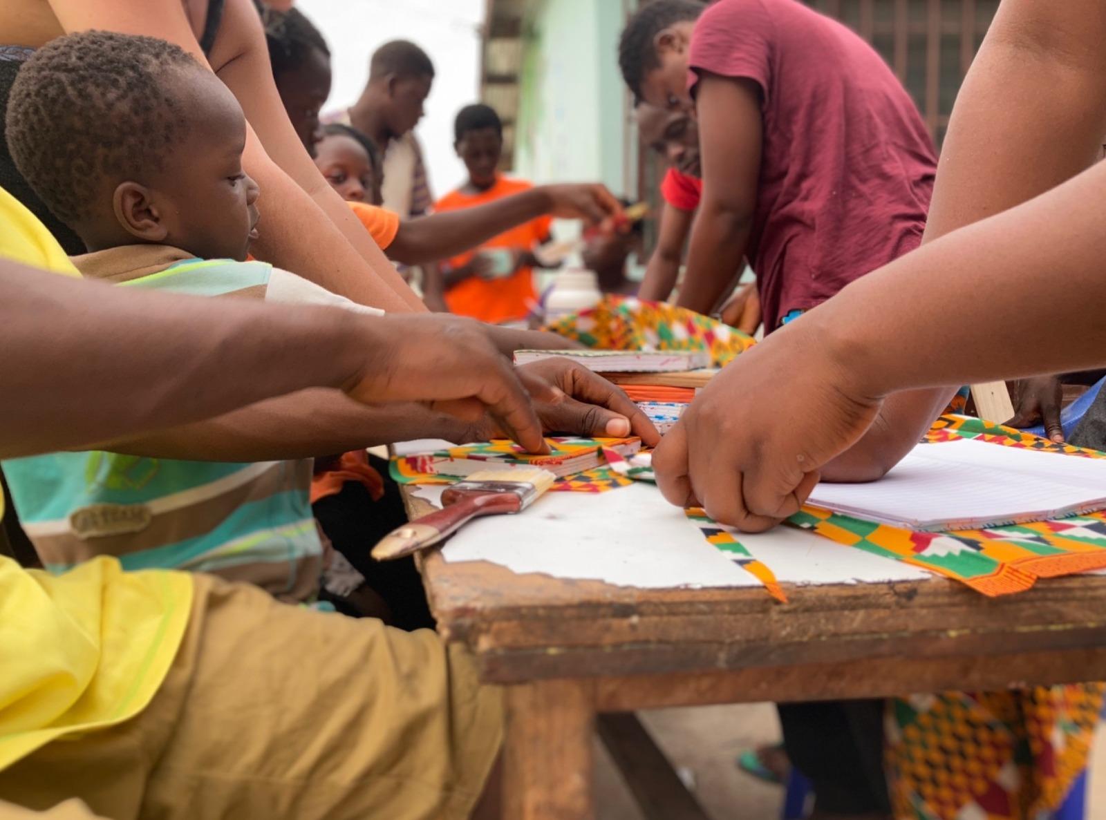 Voluntàries i infants de l'orfenat fent llibretes Font: Un llapis per Ghana